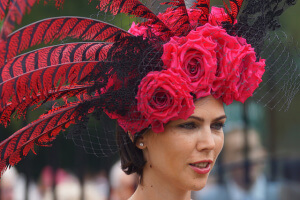 A lady wearing a red and black feather hat at the races