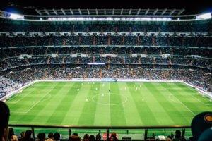 A green grass pitch inside a football stadium with football players