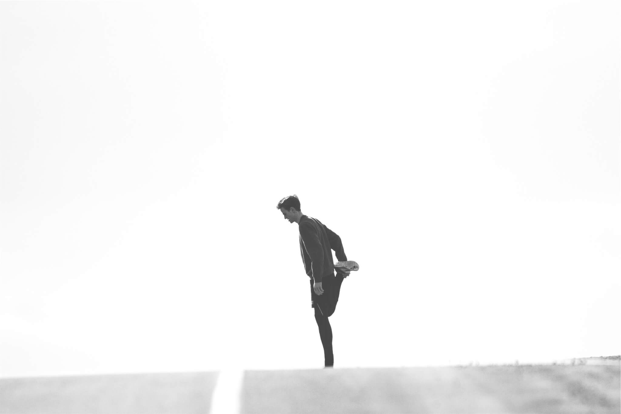 Man Stretching Black and White Sport