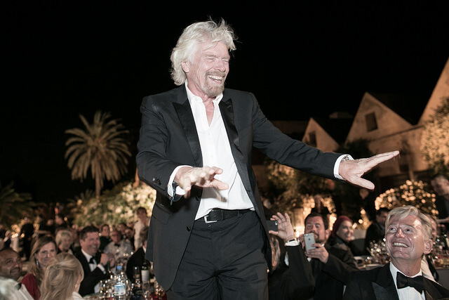 Richard Branson waving at an awards night wearing a black tux