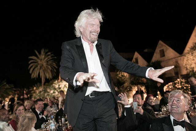 Richard Branson waving at an awards night wearing a black tux