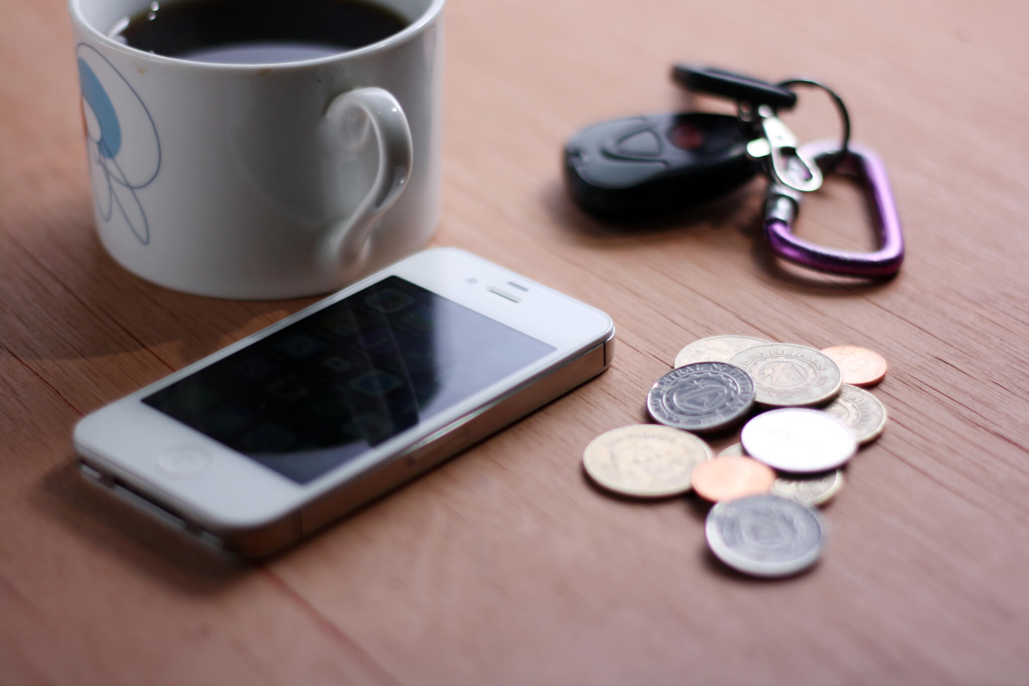 An iPhone next to cash, keys and a mug of tea on the table