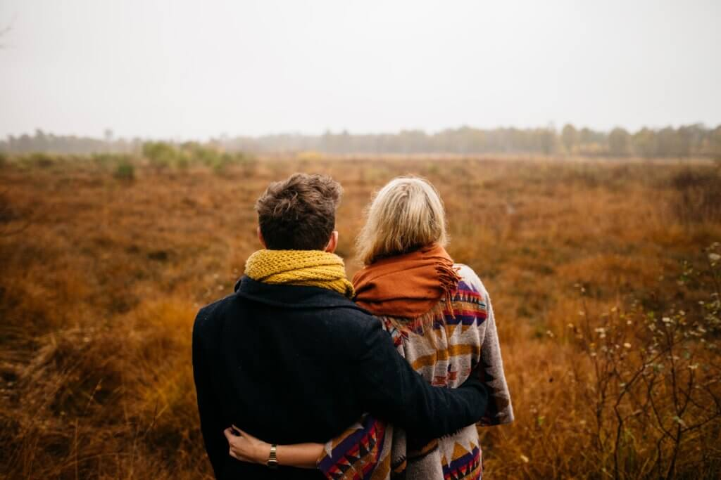 A picture of a couple hugging looking into the future in a field