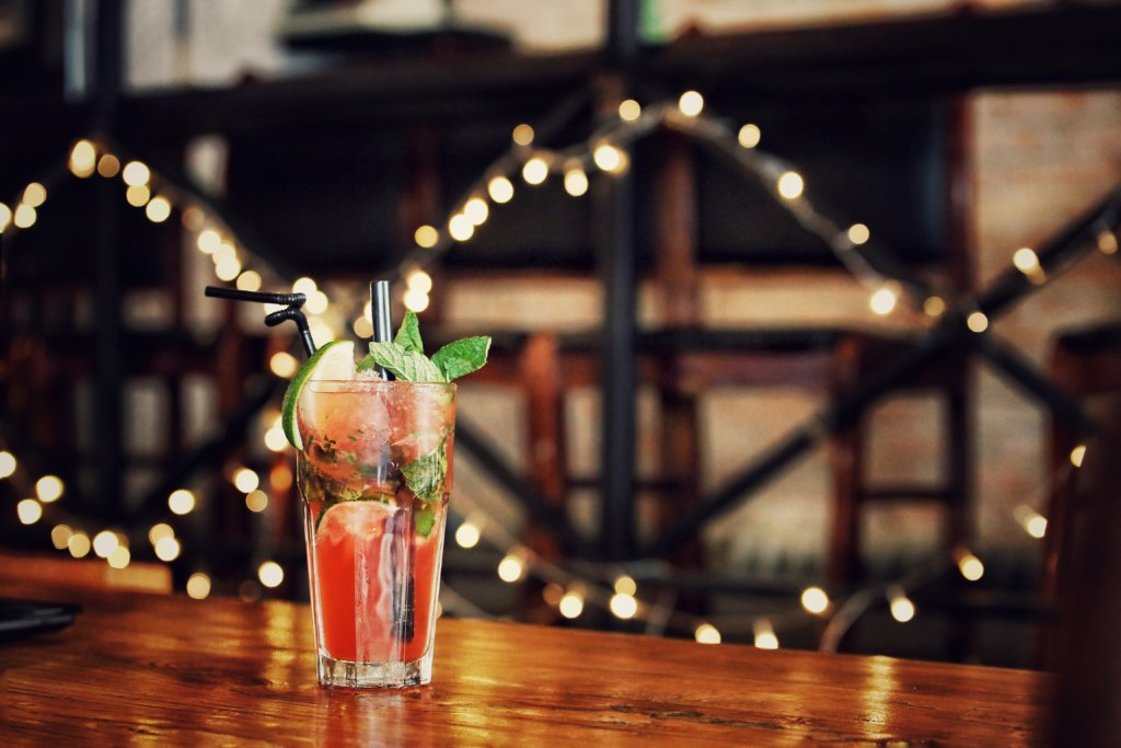A strawberry and mint cocktail with straws sitting on a table