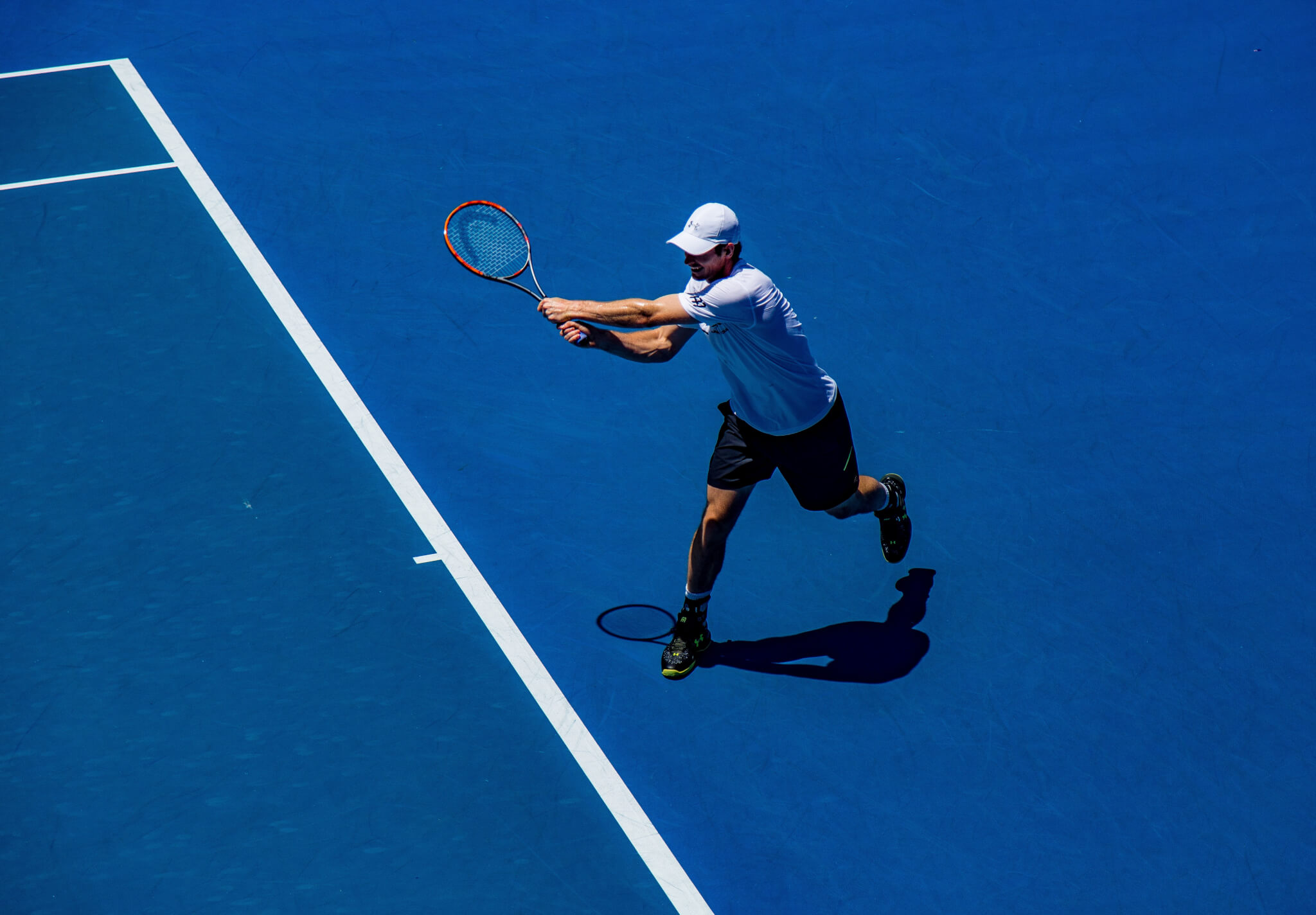 A picture of a man playing tennis on a blue court