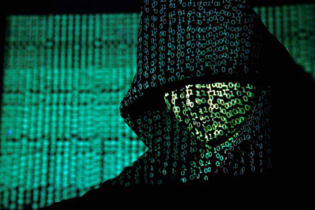 A picture of tech code hovering over a hackers face