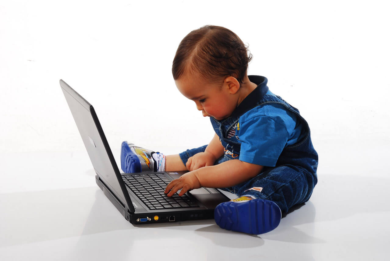 A picture of a baby using a laptop
