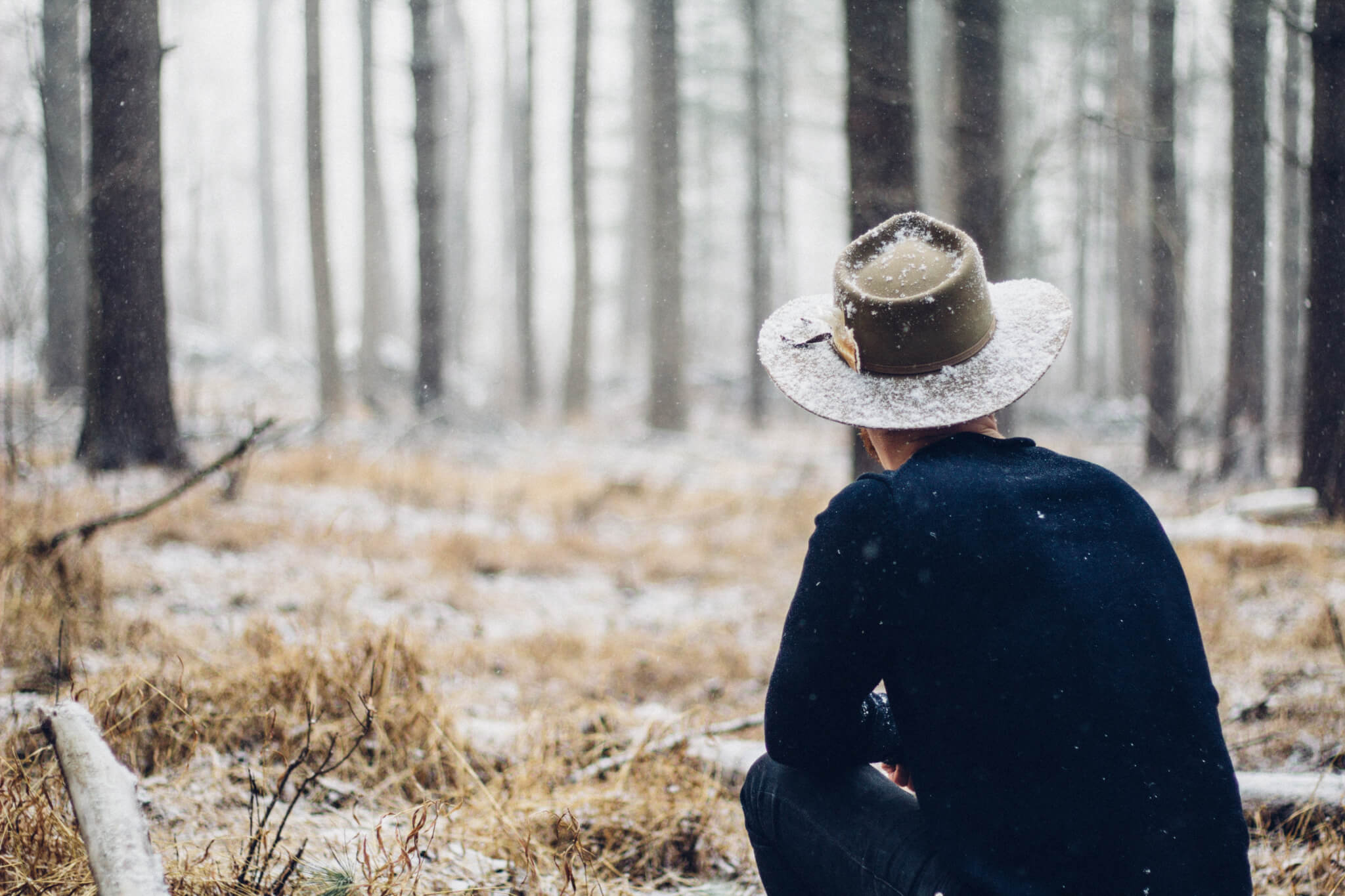 a man sitting in the woods with snow on his hat
