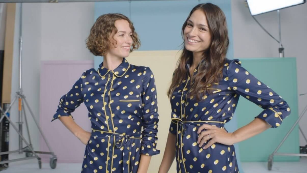 A picture of two ladies wearing matching dresses