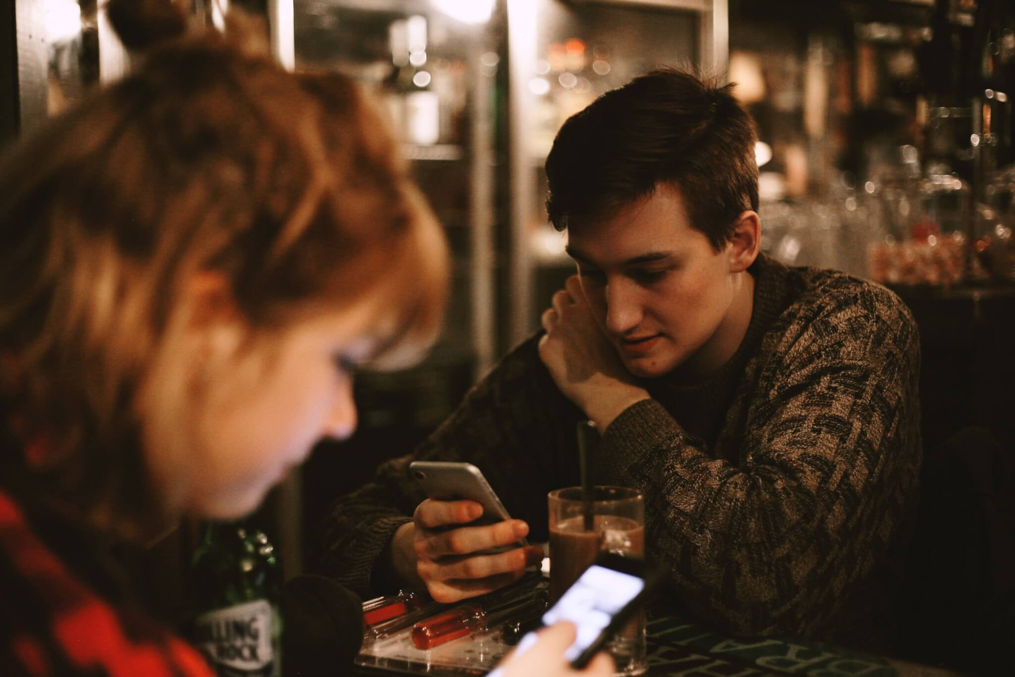 Man and women on phone whilst out socialising