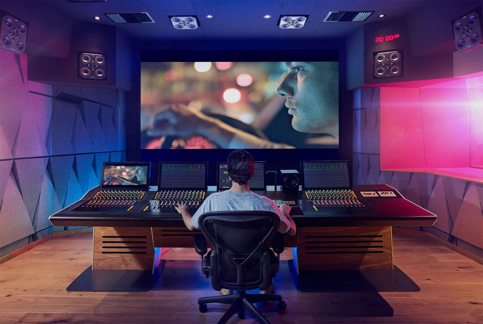 A picture of a man sitting in a film studio mixing a film