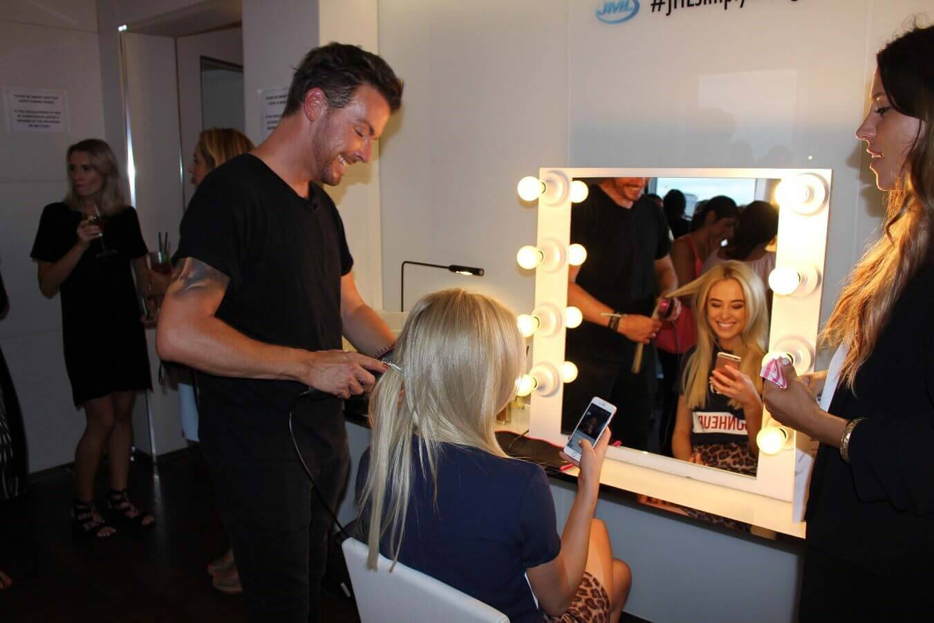 A picture of a male hairdresser doing a girls hair