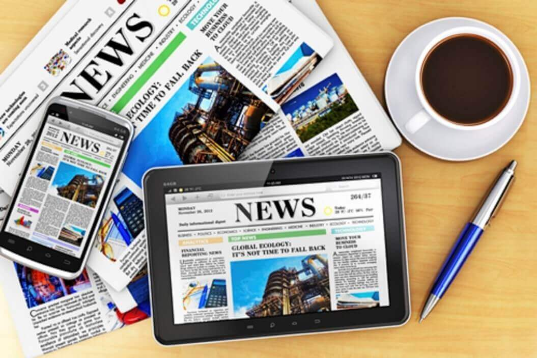 A picture of a newspaper, and ipad and an iPhone and a cup of coffee