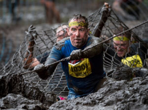 Total Warrior - participant climbing through mud