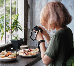 A lady taking pictures of some plates of food