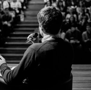 A black and white picture of a speaker talking to an audience