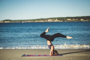a lady doing yoga on the beach in front of the sea