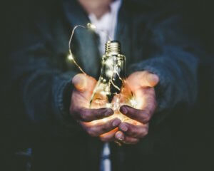 a bulb being cupped in hands and energy powering it