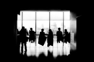 A picture of a black and white boardroom with people sitting at the table
