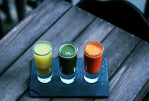 three fruit drinks in shot glasses