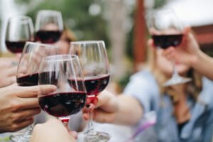 A group of people all drinking red wine in the sun