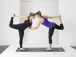 Two ladies performing a yoga pose