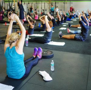 a class of people doing a yoga class inside