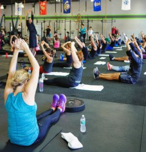 a class of people doing yoga inside