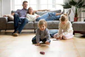Kids playing on floor, parents relaxing on sofa at home