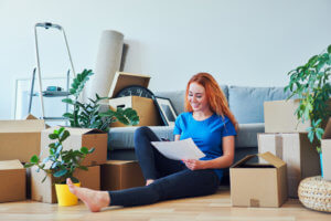 Young woman sitting on floor in new apartment with smartphone and documents