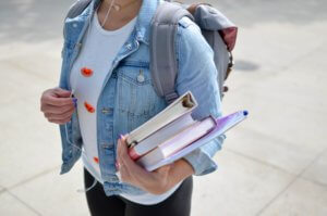 A student carrying books for class