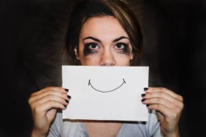 A lady crying holding up a piece of paper with a smile on it