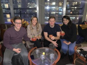 4 people having a drink at a rooftop bar