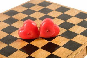 Two matching love hearts on a chess board