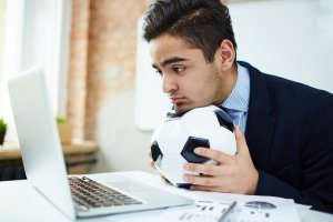 A man holding a football at his desk