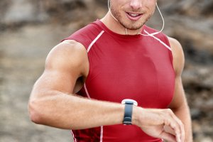 A man looking at a smart watch whilst running
