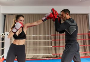 A lady throwing punches at a boxing ring