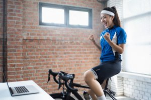 A woman cycling at home inside