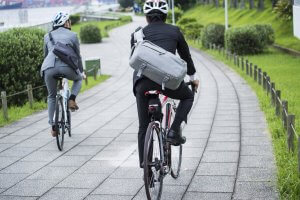 Two people cycling with helmets on